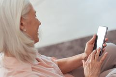 Cheerful senior woman using her smart phone at home. Smart gadget. Cheerful pleasant aged woman holding her smart phone and using it while sitting on the sofa at royalty free stock photography