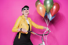 Cheerful senior woman wearing yellow leather jacket and sunglasses standing with bicycle and balloons Stock Photo