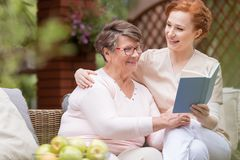 Cheerful senior woman with her tender caretaker reading a book t stock images
