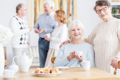 Friends from third age university. Cheerful senior women smiling at camera spending time together at nursing home in company of happy older friends from Royalty Free Stock Images