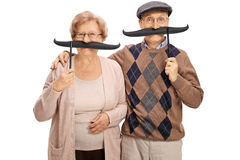Cheerful seniors with big fake moustaches Stock Photos