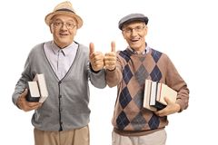 Cheerful seniors with books making thumb up gestures Royalty Free Stock Photo