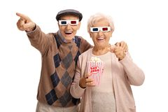 Cheerful seniors with 3D glasses and popcorn laughing and pointing royalty free stock photos
