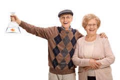 Cheerful seniors with a goldfish in a plastic bag royalty free stock images