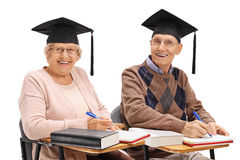 Cheerful seniors with graduation hats sitting in school chairs Stock Photography