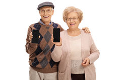 Cheerful seniors showing phones to the camera Royalty Free Stock Photography