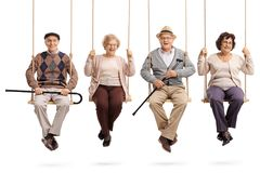 Cheerful seniors sitting on wooden swings and looking at the cam Stock Images