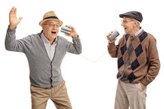 Cheerful seniors telling jokes to each other through tin can pho Royalty Free Stock Images