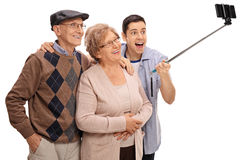 Cheerful seniors and a young man taking a selfie with a stick. Cheerful seniors and a young men taking a selfie with a stick isolated on white background Royalty Free Stock Photos