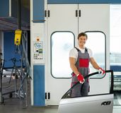 Cheerful serviceman in a car body workshop. Cheerful serviceman with car door near paint booth in a car body workshop stock photo