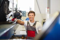Cheerful serviceman in a car body workshop Royalty Free Stock Photography