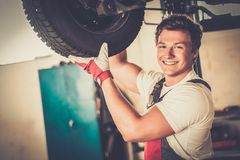 Cheerful serviceman in a car workshop Royalty Free Stock Photo