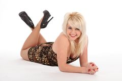 Cheerful sexy blonde girl in short dress on floor Royalty Free Stock Photo