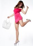 Cheerful sexy woman. A sexy and spirited woman in a tiny red dress. Her left arm and leg are flung back and she is carrying a white bag and wearing clear high Stock Photos