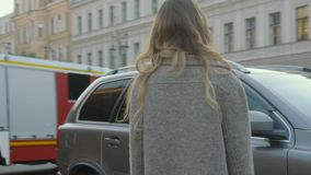 Smiling girl entertains on a city street with a baroque building and cars in slo-mo stock video