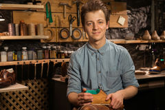 Cheerful shoemaker in workshop holding shoes. Photo of young cheerful shoemaker in workshop holding shoes. Looking at camera Royalty Free Stock Images