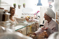 Cheerful shop woman offering female client nuts and smiling. Cheerful shop women offering matur female clien nuts and smiling stock photography
