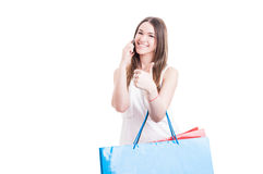 Cheerful shopaholic talking on cellphone and showing like sign Royalty Free Stock Image
