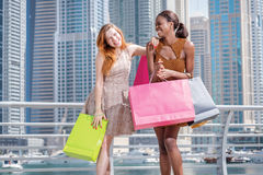 Cheerful shopaholics. Two beautiful girl-friends in dresses hold. Ing shopping bags in their hands on the promenade while embraced and laughing with shopping Stock Photo