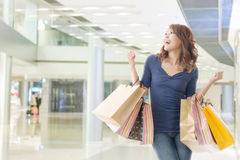 Cheerful shopping woman. Of Asian holding bags Stock Photography
