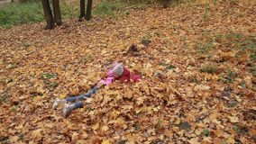 Cheerful siblings jumping in pile of autumn leaves stock video footage