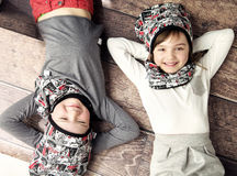 Cheerful siblings lying on the wooden floor Royalty Free Stock Photos