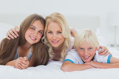 Cheerful siblings and mother lying on bed Stock Photos