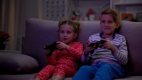 Cheerful siblings playing video game using console at night instead of sleeping. Stock photo stock image