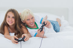 Cheerful siblings playing video games. While they are lying on bed Stock Images