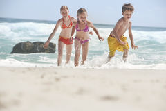 Cheerful Siblings Running In Water Royalty Free Stock Photos