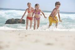 Cheerful Siblings Running In Water Royalty Free Stock Photos