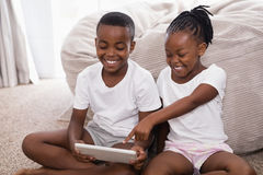 Cheerful siblings using digital tablet while sitting on rug Stock Images