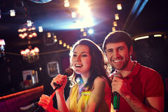 Cheerful singing couple in karaoke Royalty Free Stock Images