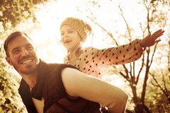 Cheerful single father carrying his daughter. On piggyback and enjoying in park royalty free stock image