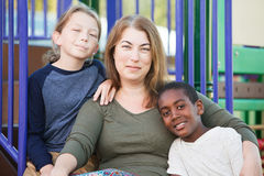 Cheerful single mom with sons outside. Single mother sitting with cute male children at park together Royalty Free Stock Photo
