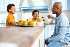 Cheerful single-parent family discussing plan for the day royalty free stock photo
