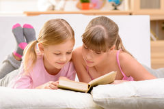 Cheerful sisters reading book Royalty Free Stock Image
