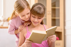 Cheerful sisters reading book Royalty Free Stock Photos