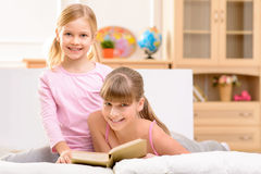 Cheerful sisters reading book Stock Images