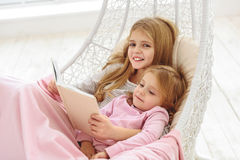 Cheerful sisters reading interesting story Royalty Free Stock Images