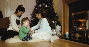 Cheerful sisters wrapping Christmas gift for parents near Christmas tree . Cute son eating apple and looking away. Red. Epic 4k 2016 stock video footage