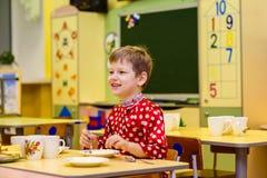 Cheerful six year old boy having Breakfast in kindergarten stock photos
