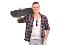 Cheerful skater holding a skateboard. Cheerful young skater in a checkered shirt holding a skateboard over his shoulder and looking at the camera isolated on Stock Images