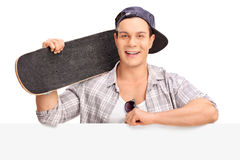 Cheerful skater posing behind a billboard Royalty Free Stock Photography