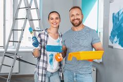 Cheerful skilled painters standing together. Our project. Content professional painters smiling and holding a roller and brush Royalty Free Stock Photo