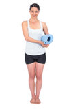 Cheerful slender model holding her rolled up mat Stock Image