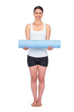 Cheerful slender model posing holding her rolled up mat Stock Image