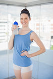 Cheerful slender woman holding plastic flask Stock Images
