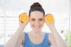 Cheerful Slender Woman In Sportswear Holding Slices Of Orange Royalty Free Stock Image