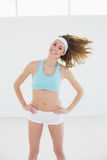 Cheerful slender woman posing in sports hall with hands on hips Royalty Free Stock Image